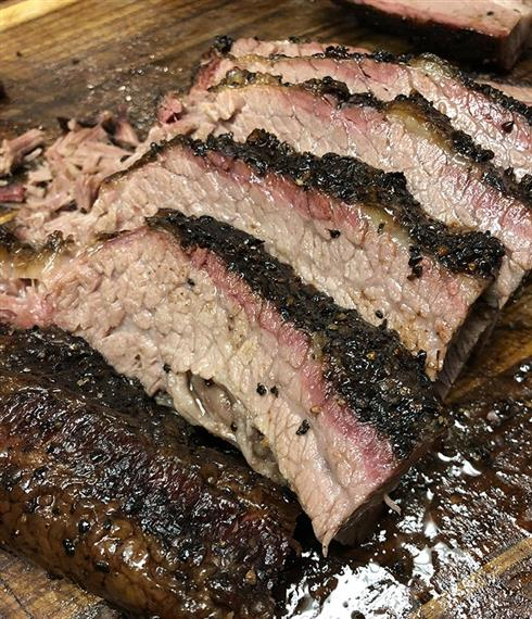 Sliced barbecue brisket on cutting board