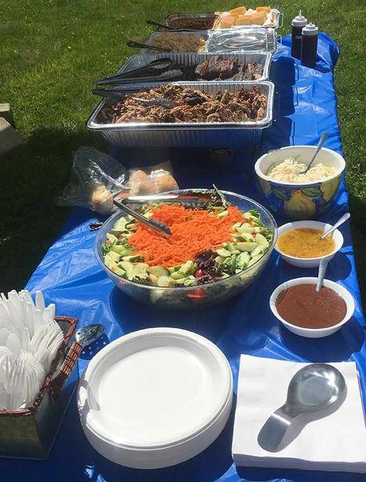 Catering spread on long table. Pork, ribs, beans, mac & cheese, cornbread, salad.