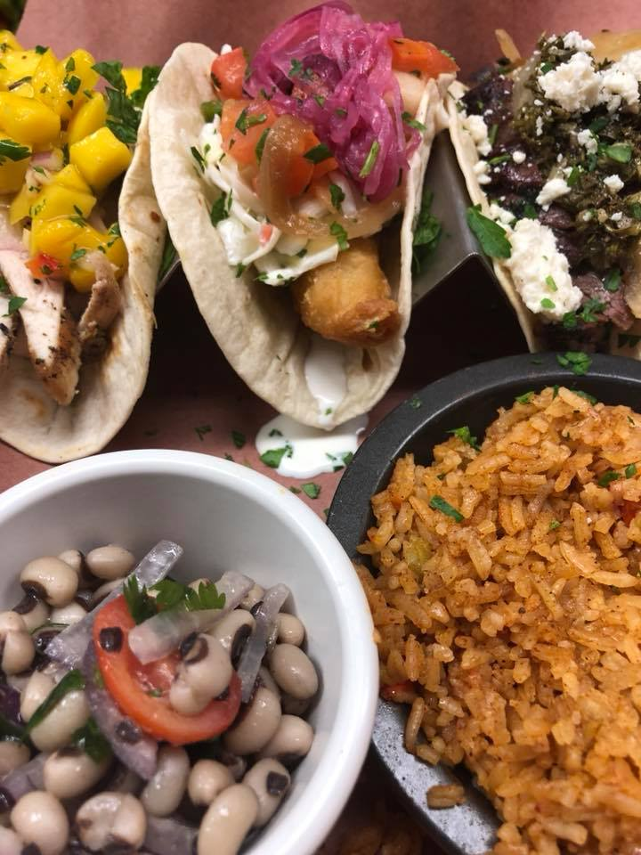 Tacos with chicken, beef, cheese, tomatoes. Sides of rice and beans.