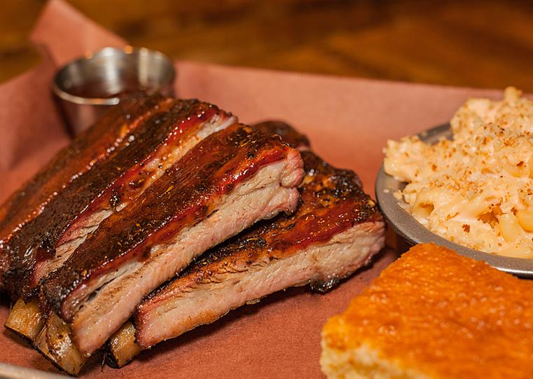 barbecue ribs with side of sauce, coleslaw and corn bread