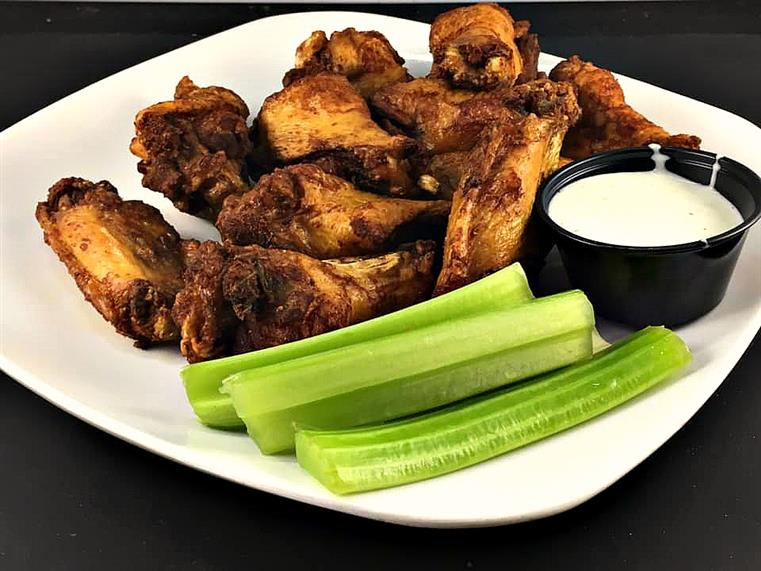 trashed wings with a side of ranch and celery sticks