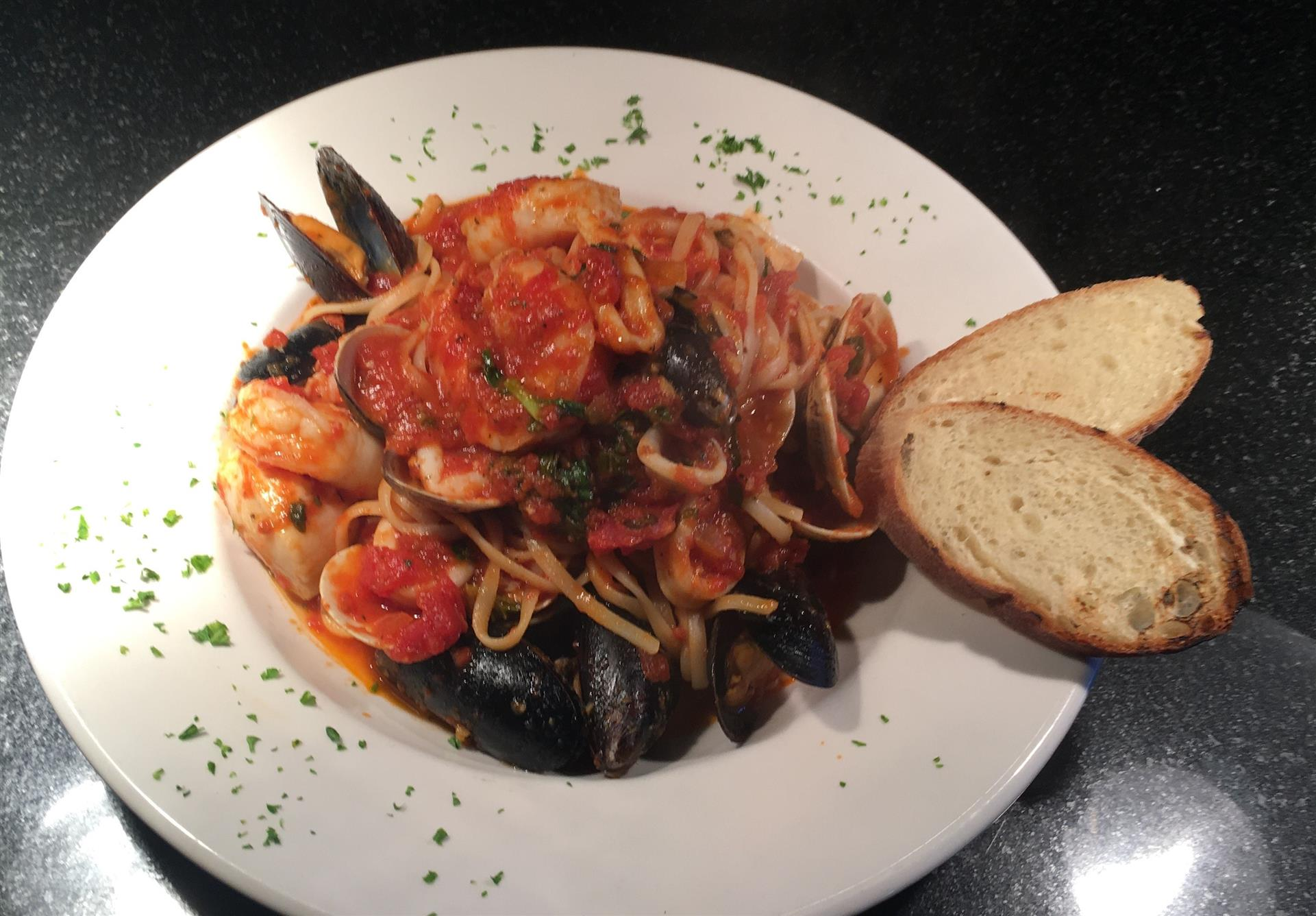 Seafood Cioppino. Scallops, Shrimp, Clams, Mussels and Calamari topssed with linguine in marinara sauce.