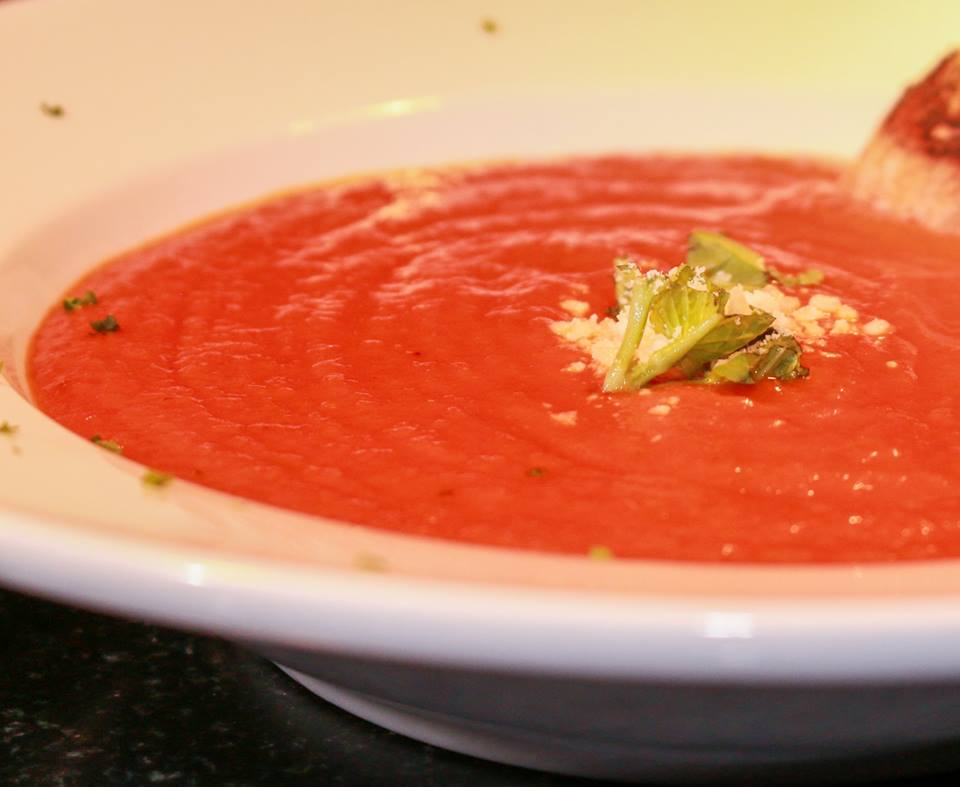 bowl of tomato sauce garnished with basil leaves.