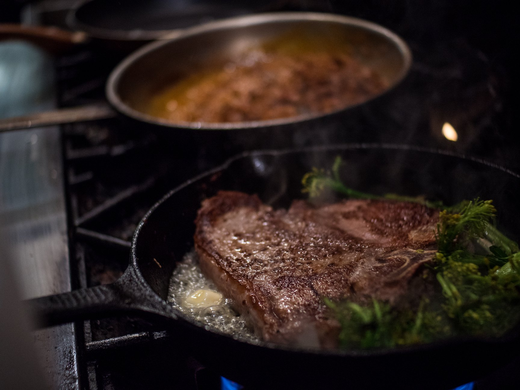 porterhouse steak on a sizzling pan with butter and seasonings.