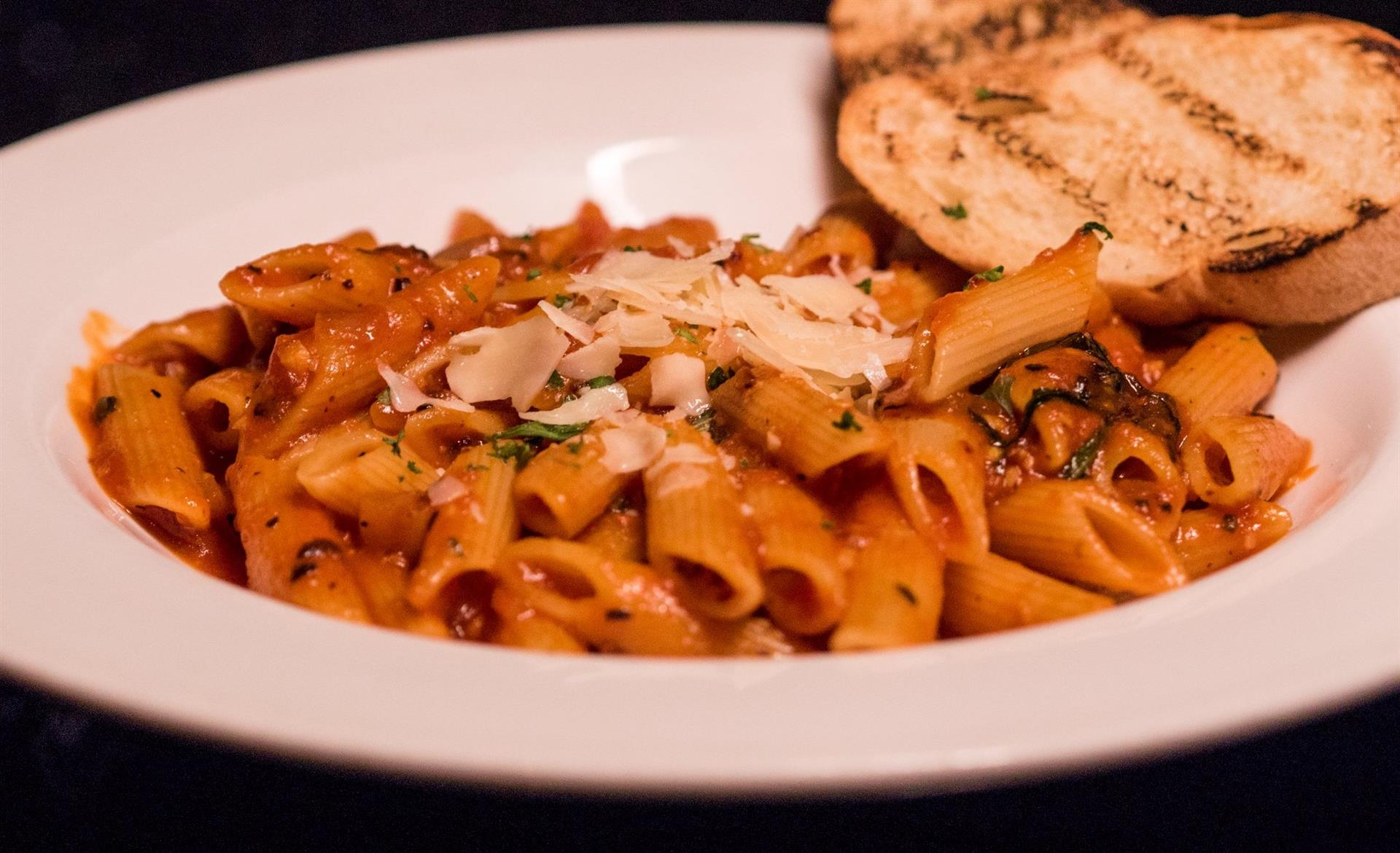 Penne pasta in tossed in tomato sauce and topped with fresh shaved parmesan cheese. Garlic bread on the side.
