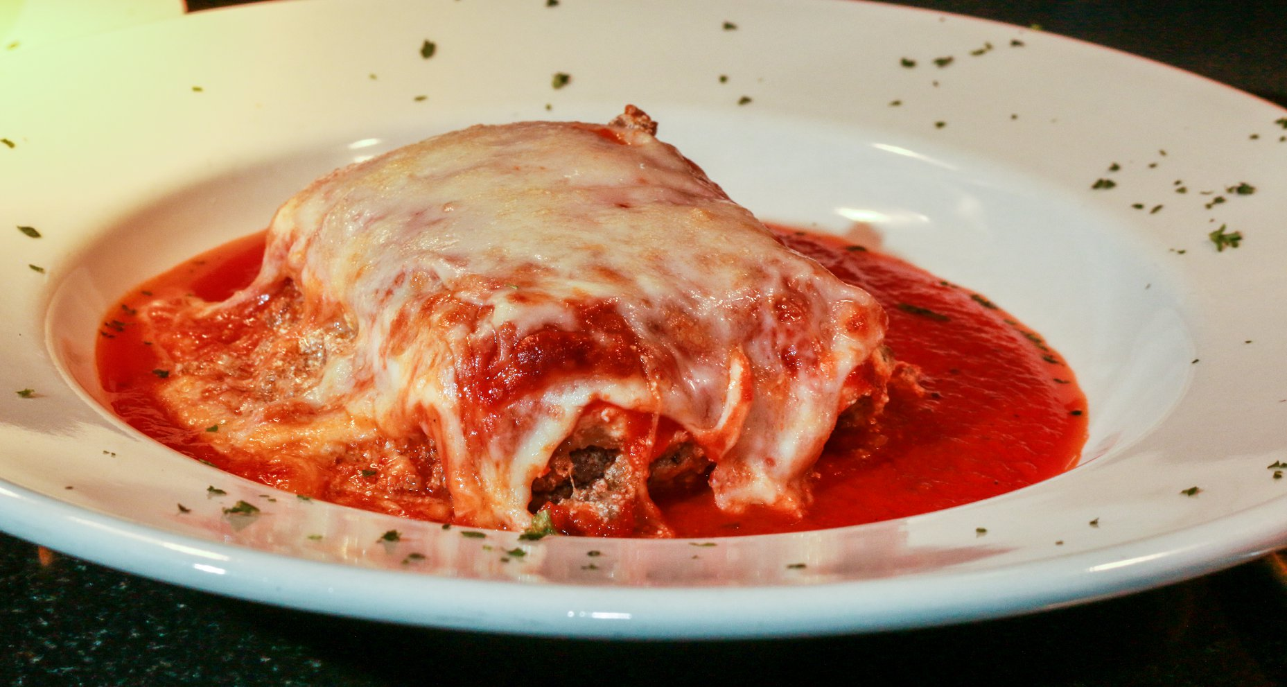 Baked lasagna on a plate topped with marinara sauce and melted mozzarella cheese.
