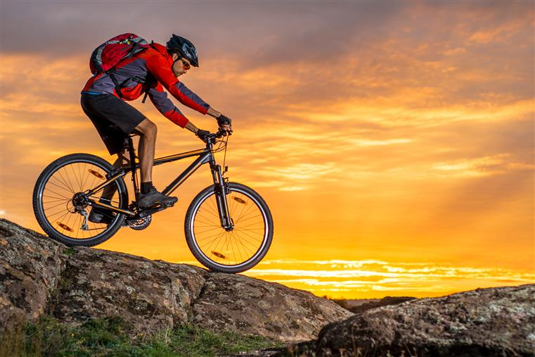 man riding a mountain bike down a slope with the sunset behind him