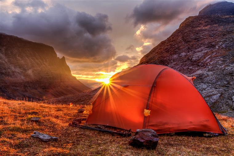 tent in the mountains with sun beams shining in through mountains behind it