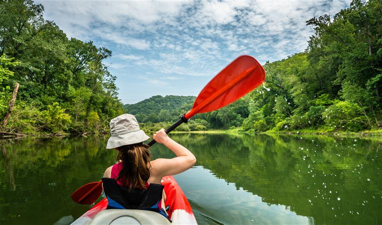 girl paddling down a river on a kayak with trees around her and a blue sky filled with puffy clouds on a sunny day
