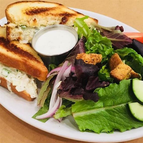 homemade chicken salad sandwich on marble rye bread with a side salad topped with red onions, cucumbers and croutons with a side of ranch