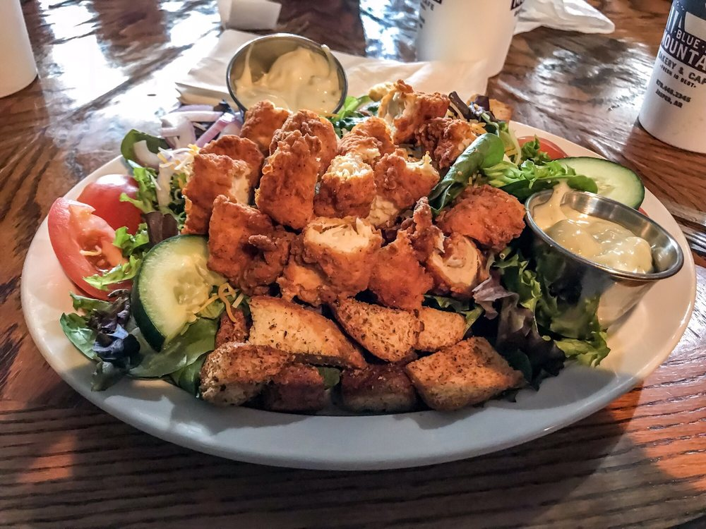 salad with mixed greens, tomatoes, cucumbers and crispy chicken and croutons served with a side of creamy dressing