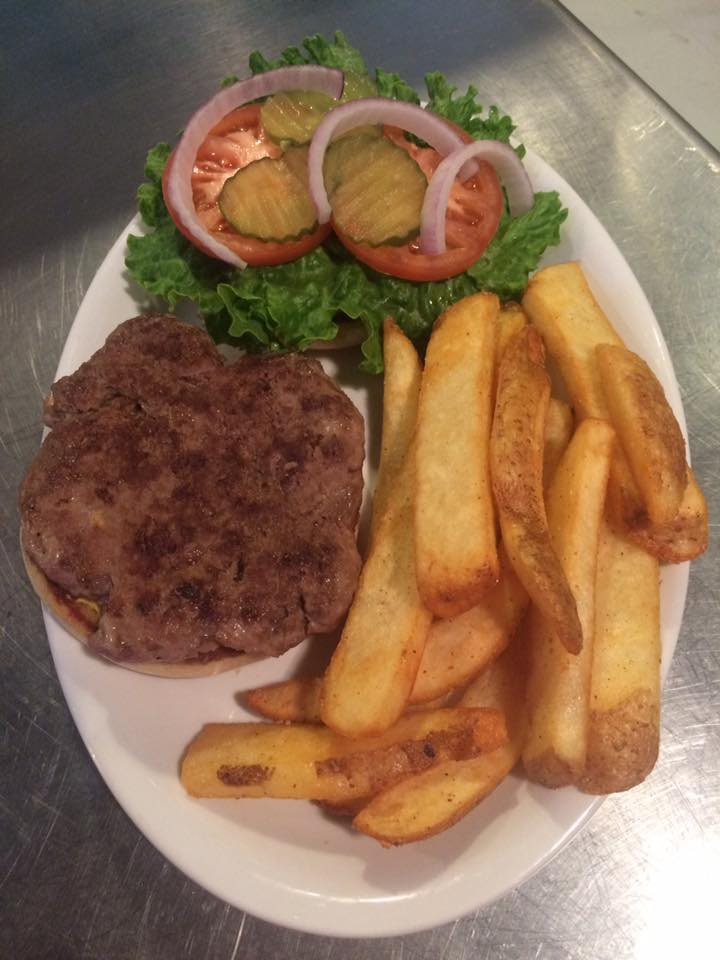 turkey burger on a roll with lettuce, tomato, pickles and red onion on side served with thick steak cut french fries