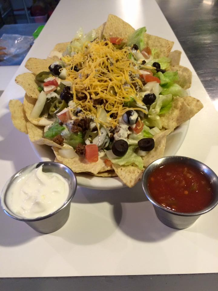 taco salad in tortilla bowl with onions, lettuce, tomato, olives, shredded cheese and a side of sour cream and salsa