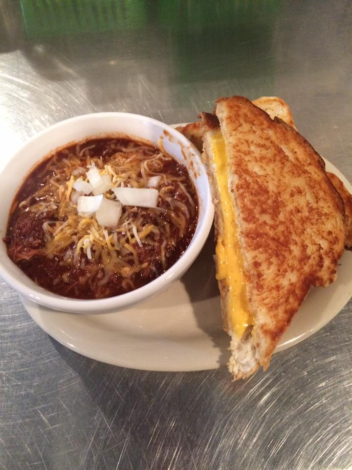 chili with shredded cheese and white onion with a grilled cheese