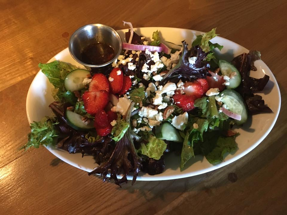 mixed greens salad topped with red onion, cucumbers, crumbled feta and strawberries served with balsamic vinaigrette