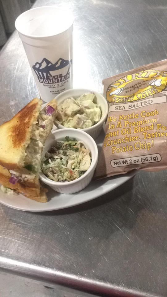 chicken salad sandwich on toasted bread served with 2 side salads and a bag of sea salted kettle chips