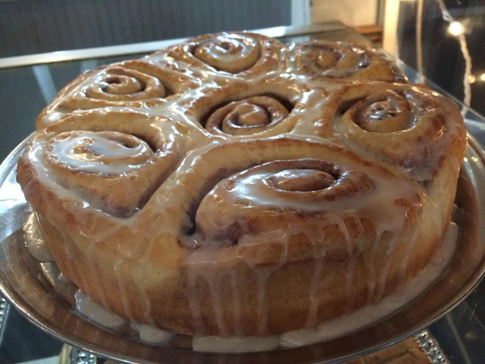 homemade cinnamon bun cake drizzled with dripping icing
