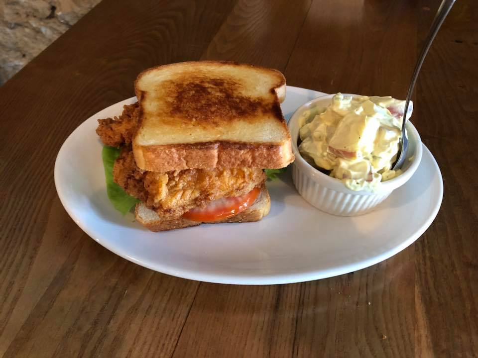 crispy fried chicken on bread with lettuce and tomato, served with a side of potato salad