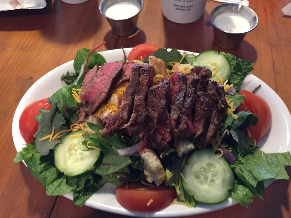 strips of rare steak served over a salad of mixed greens, cucumbers, tomatoes, shredded cheese. served with a side of blue cheese