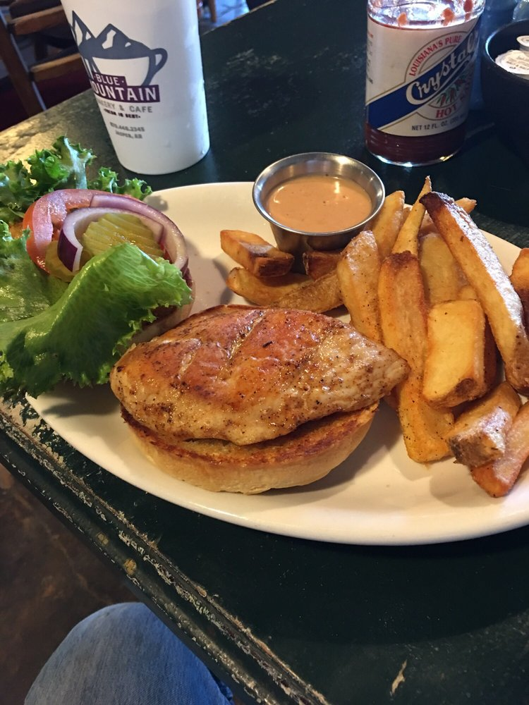 grilled chicken patty on a roll with lettuce, tomato, pickles, and red onion on the site. served with a side of steak cut frnch fries and a pink creamy sauce
