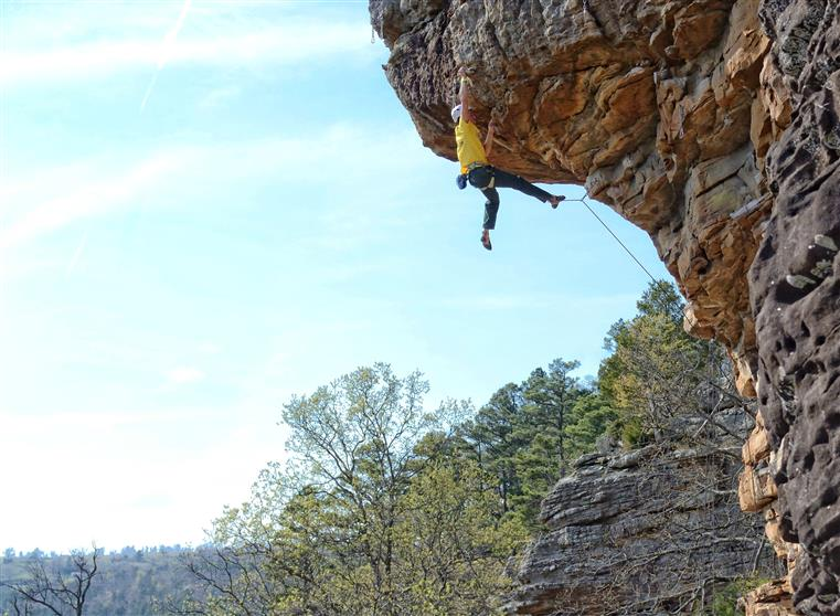 man rock climbing on bluffs in arkansas