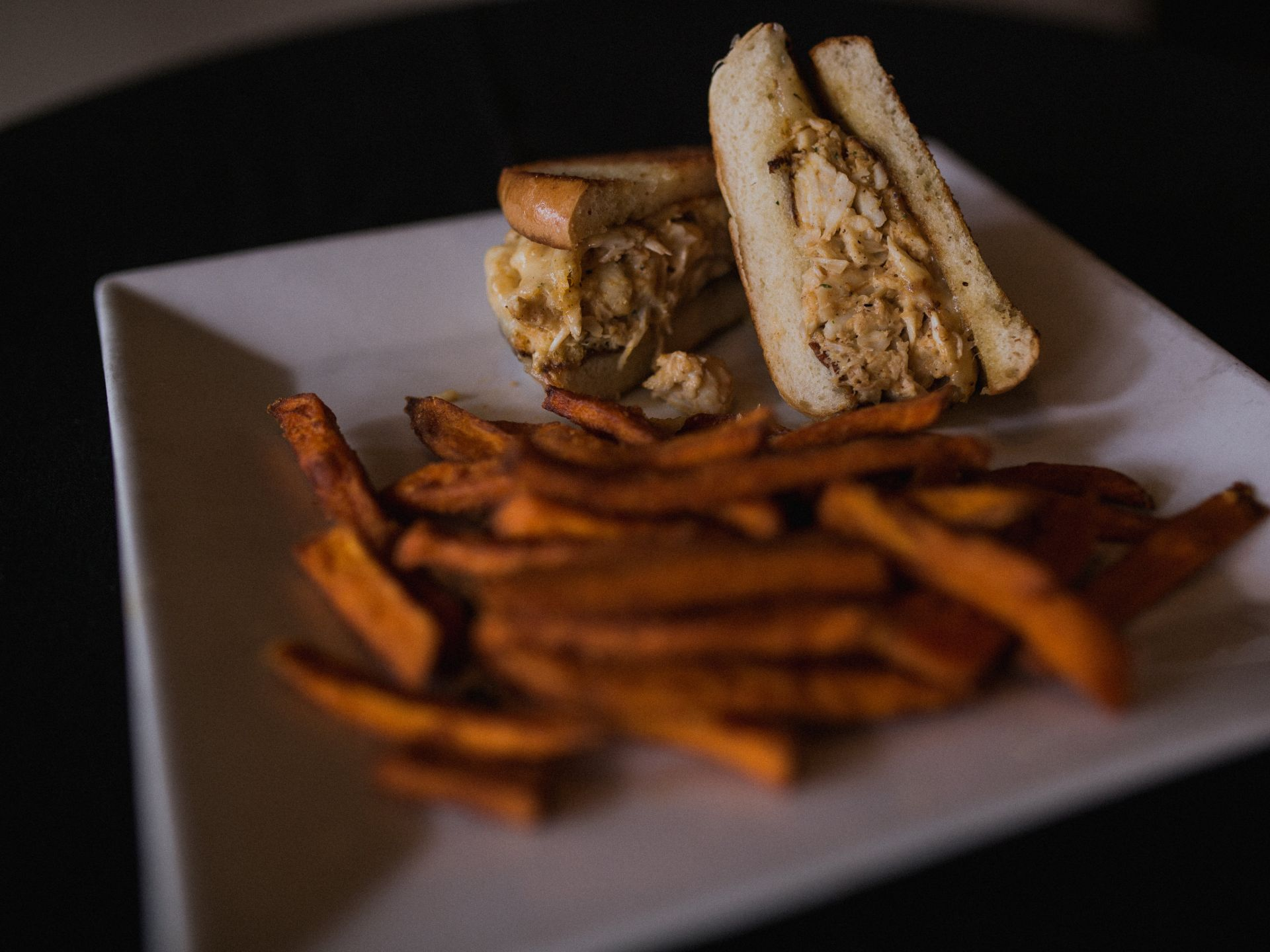Crab cake melt on a plate with sweet potato fries