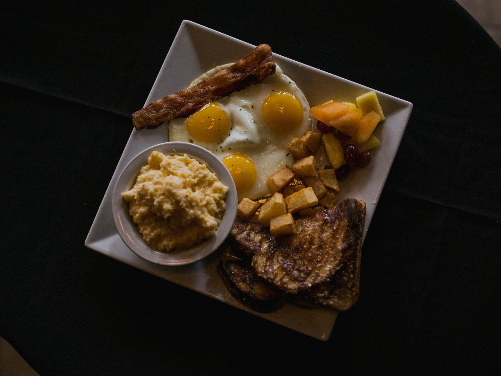 Top-down view of three fried eggs on a plate with breakfast potatoes, fresh cut fruit, bacon strip, French toast and a bowl of oatmeal