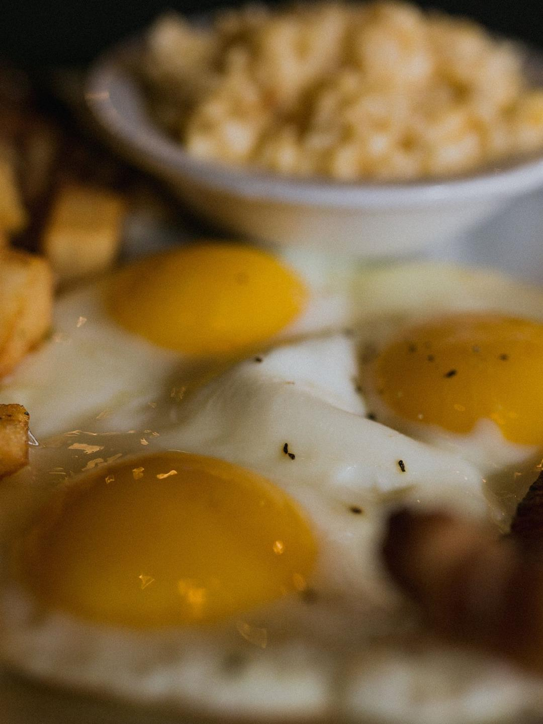 Three fried eggs on a plate with breakfast potatoes