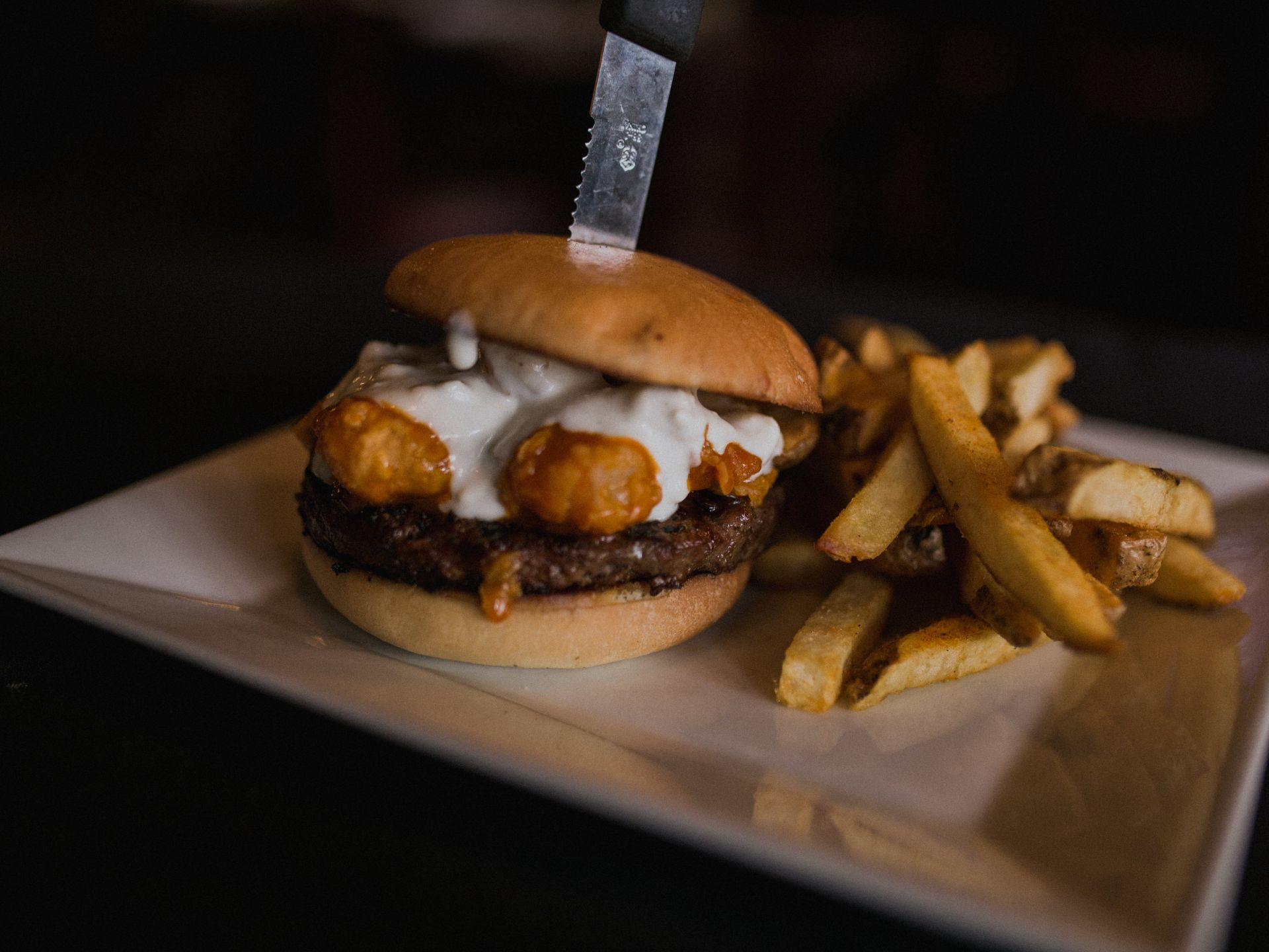 Buffalo surf and turf burger with shrimp and bleu cheese dressing with a knife through the center and French fries