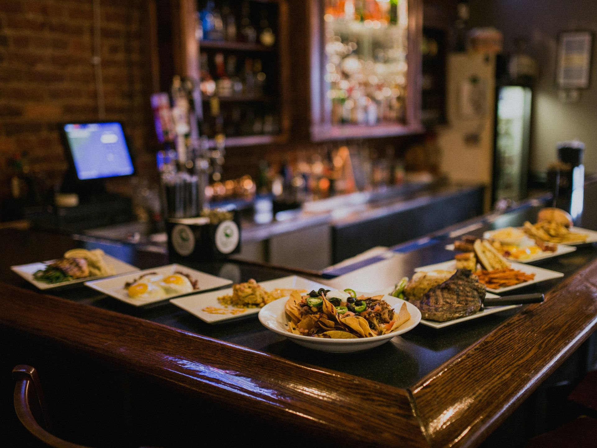An assortment of plated entrees and appetizers on a bar-top