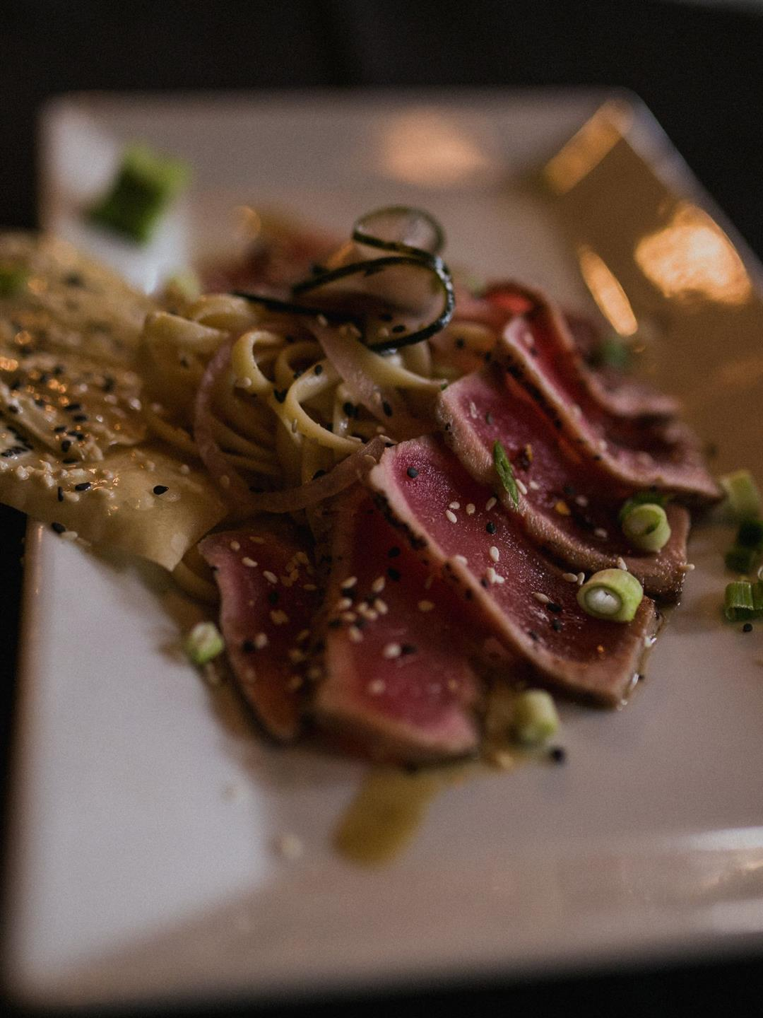Seared tuna with scallions and sesame seeds on a plate with sesame tortilla chips