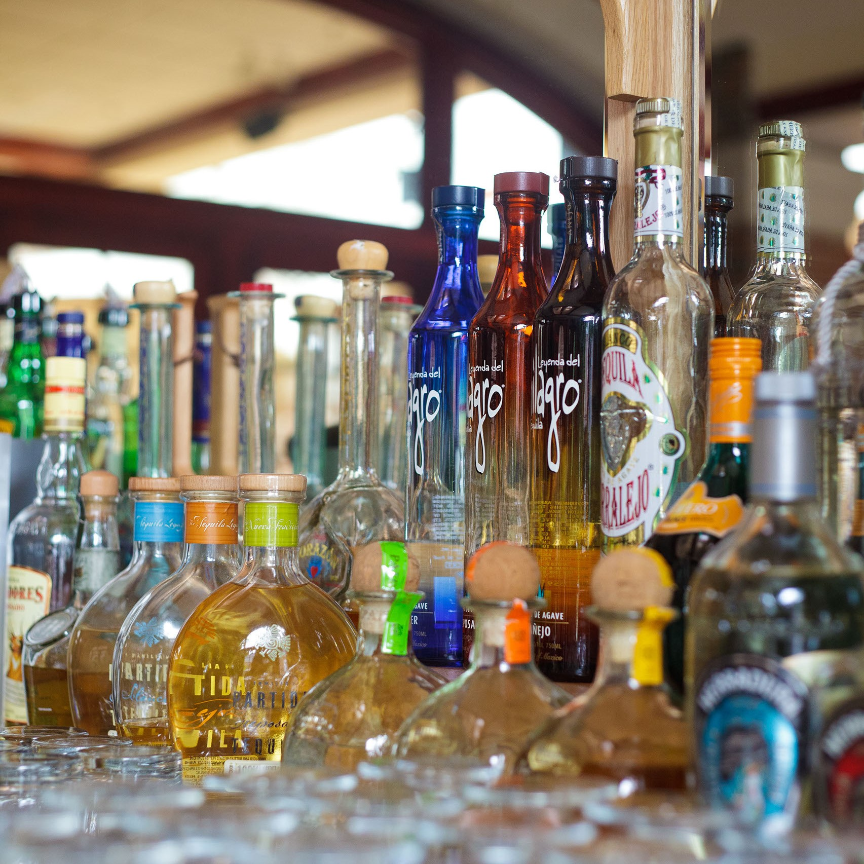 various liquor and tequila bottles lined up on bar