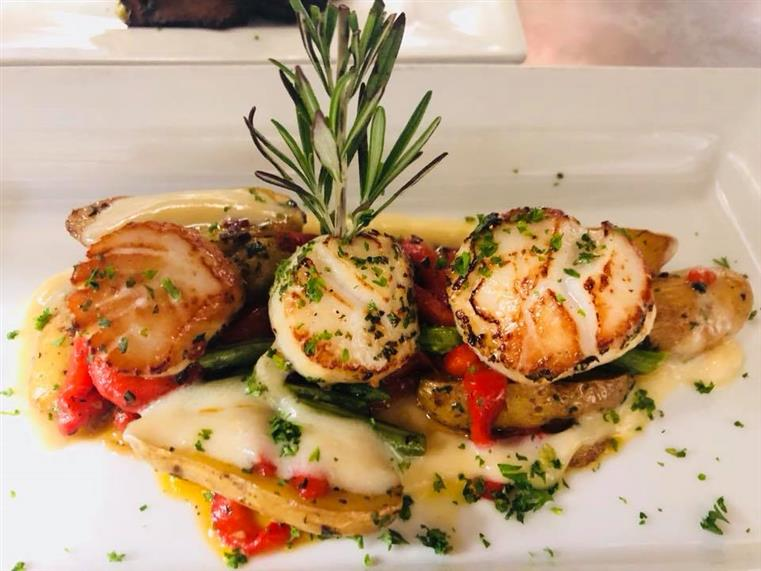 Sauteed scallops on a plate with roasted red peppers, artichokes and rosemary