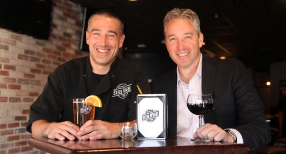 Executive Chef Bryan Tortorella and Managing Partner Glenn Carlough posing for a picture sitting at a table with a glass of beer and a glass of red wine