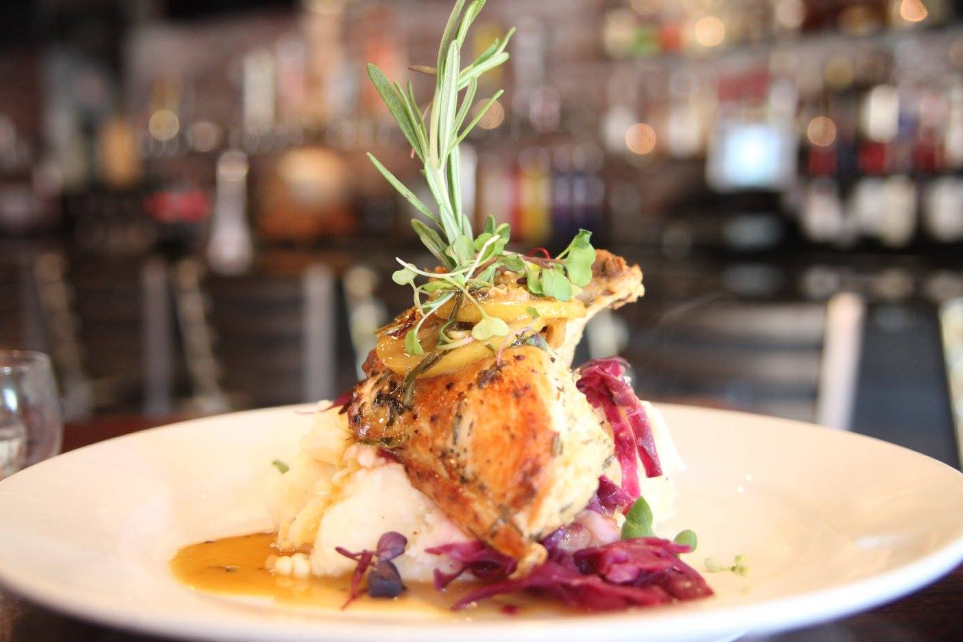 Roasted chicken over mashed potates and red onions with rosemary