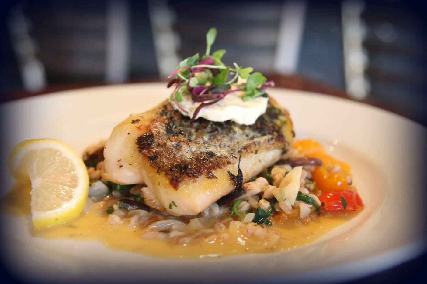 Pan seared cod over white beans and roasted peppers with a lemon wedge