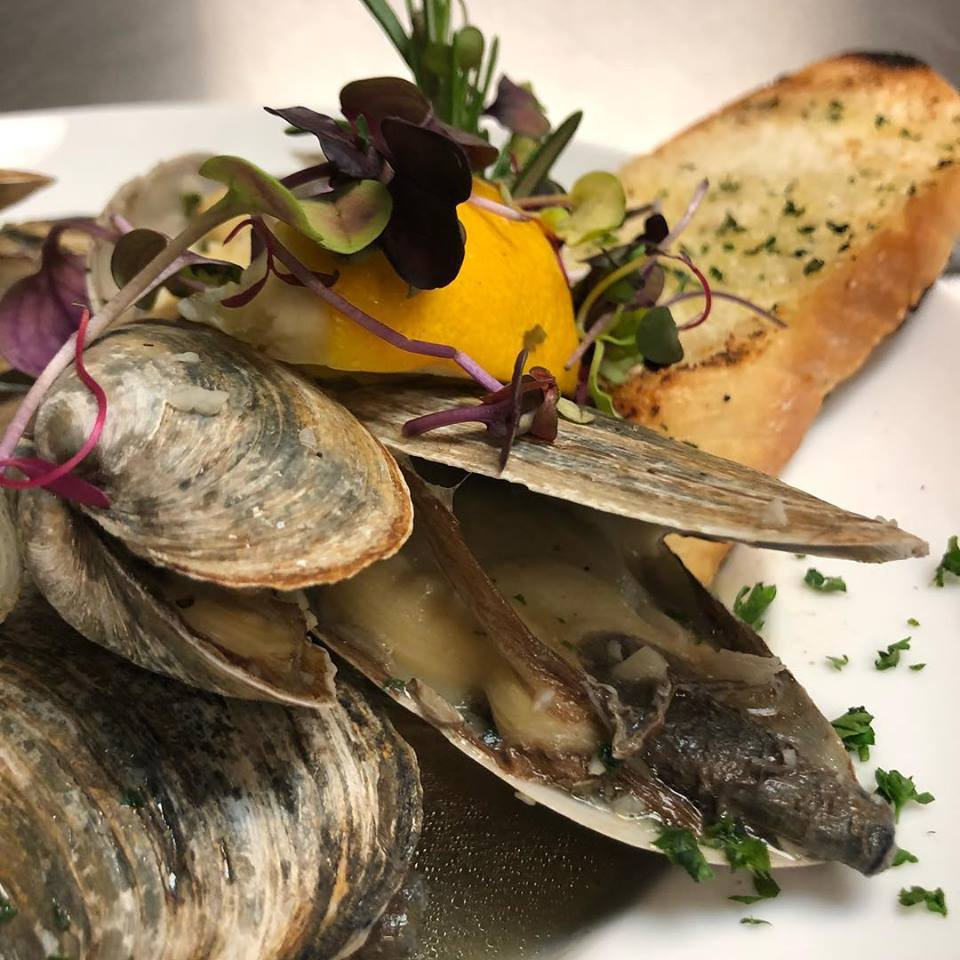 Steamed clams with herbs over toasted garlic bread