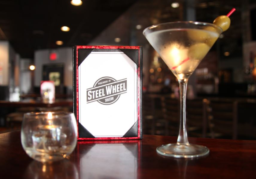 Steel Wheel branded menu on a table with a martini and a glass of whiskey
