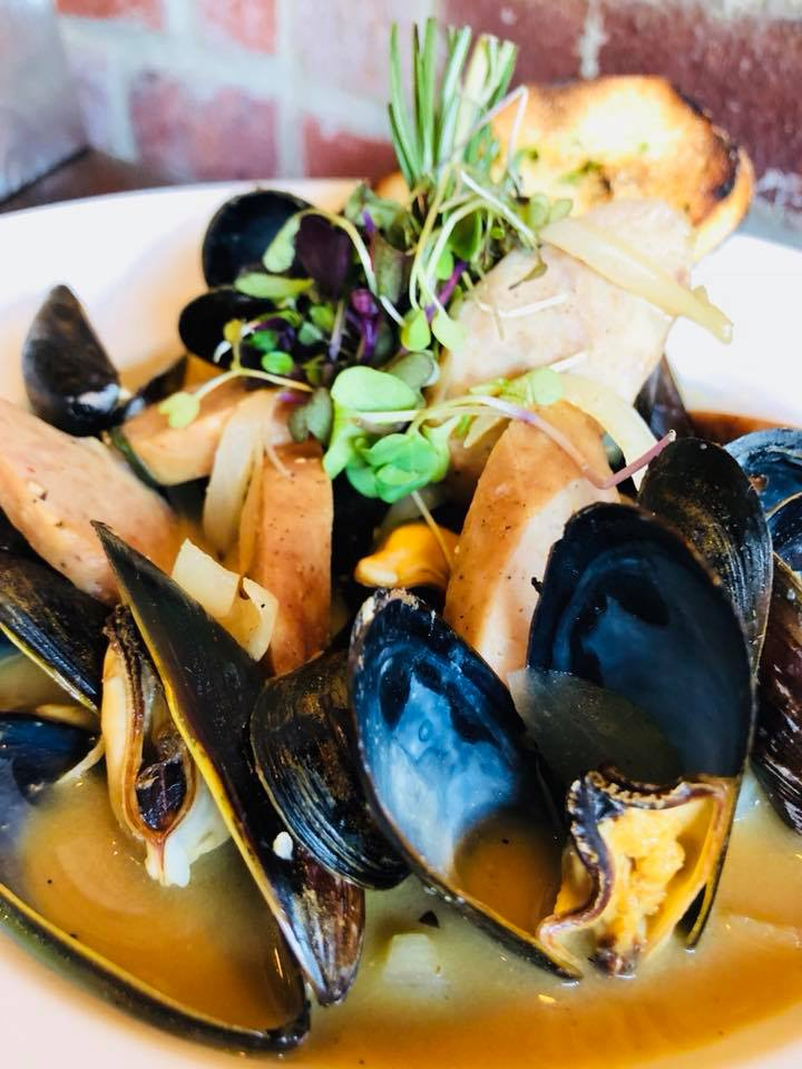 Steamed mussles in a bowl with toasted bread slices and assorted greens