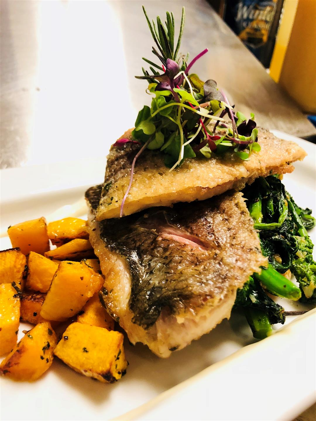 two pieces of fish on a plate with sweet potatoes and spinach on a white plate and garnished