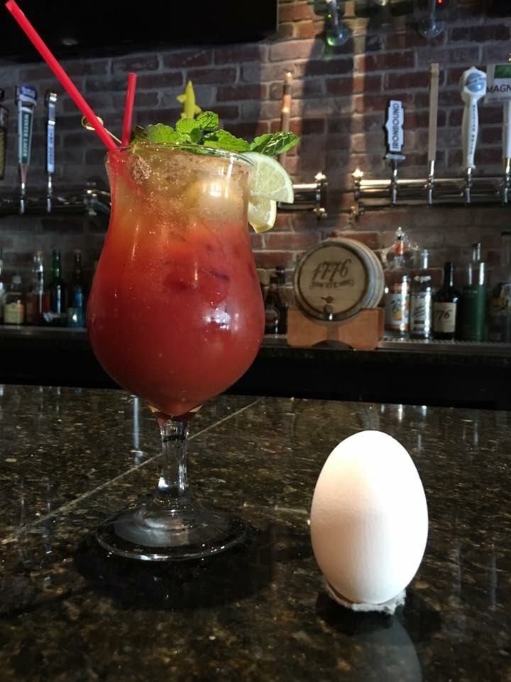 a bloody mary in a glass with two slices of lemon and garnish next to an egg