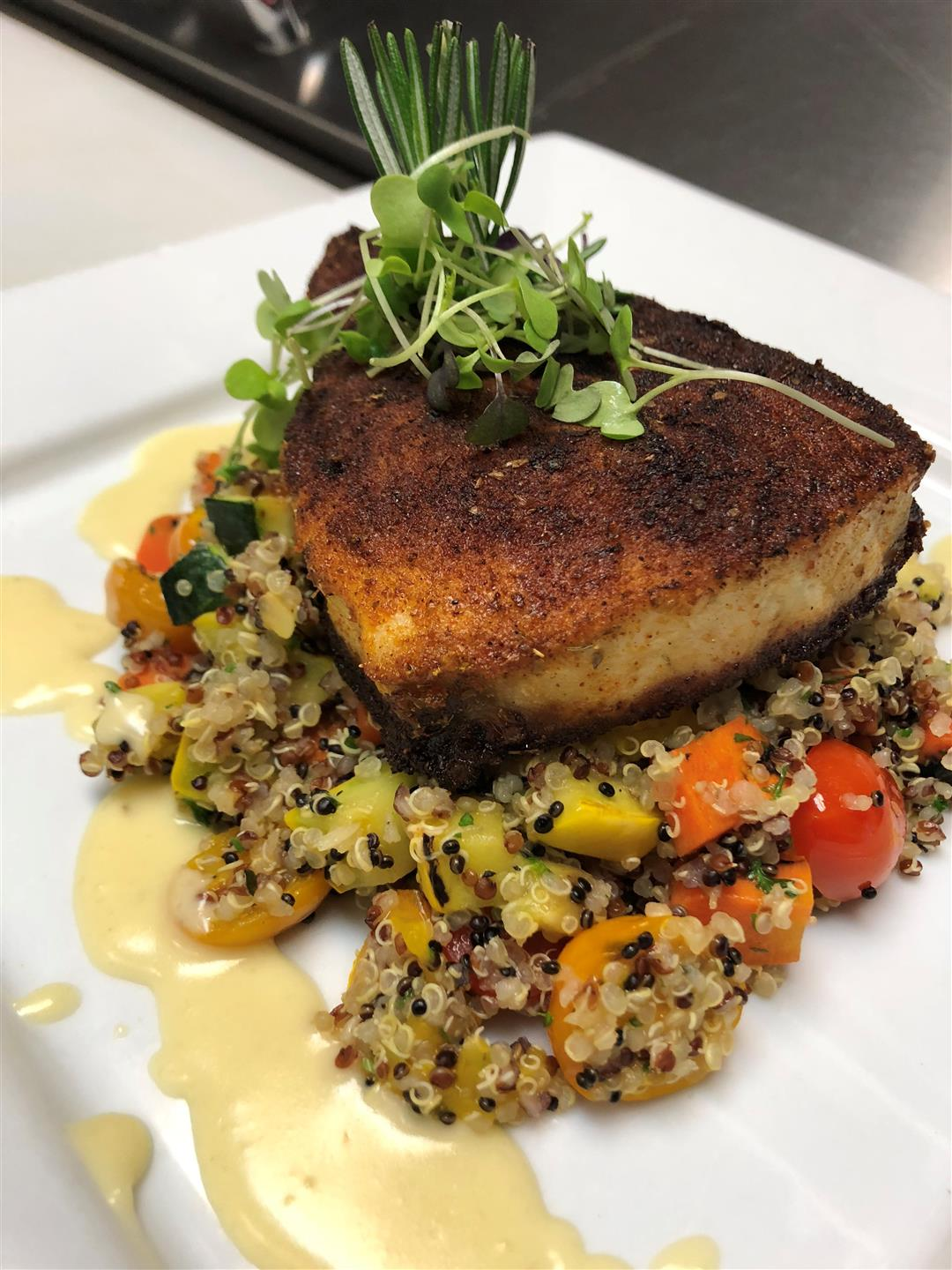 a baked fish dish on a bed of quinoa and mixed vegetables with cream sauce and garnished on a white plate