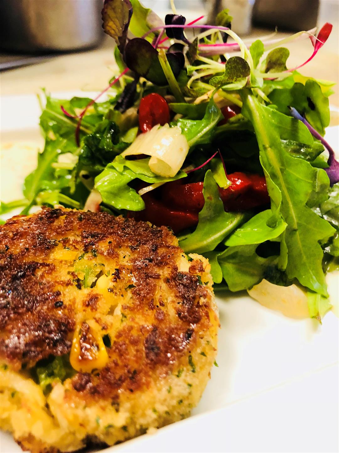 a crab cake next to a salad with beets on a white plate