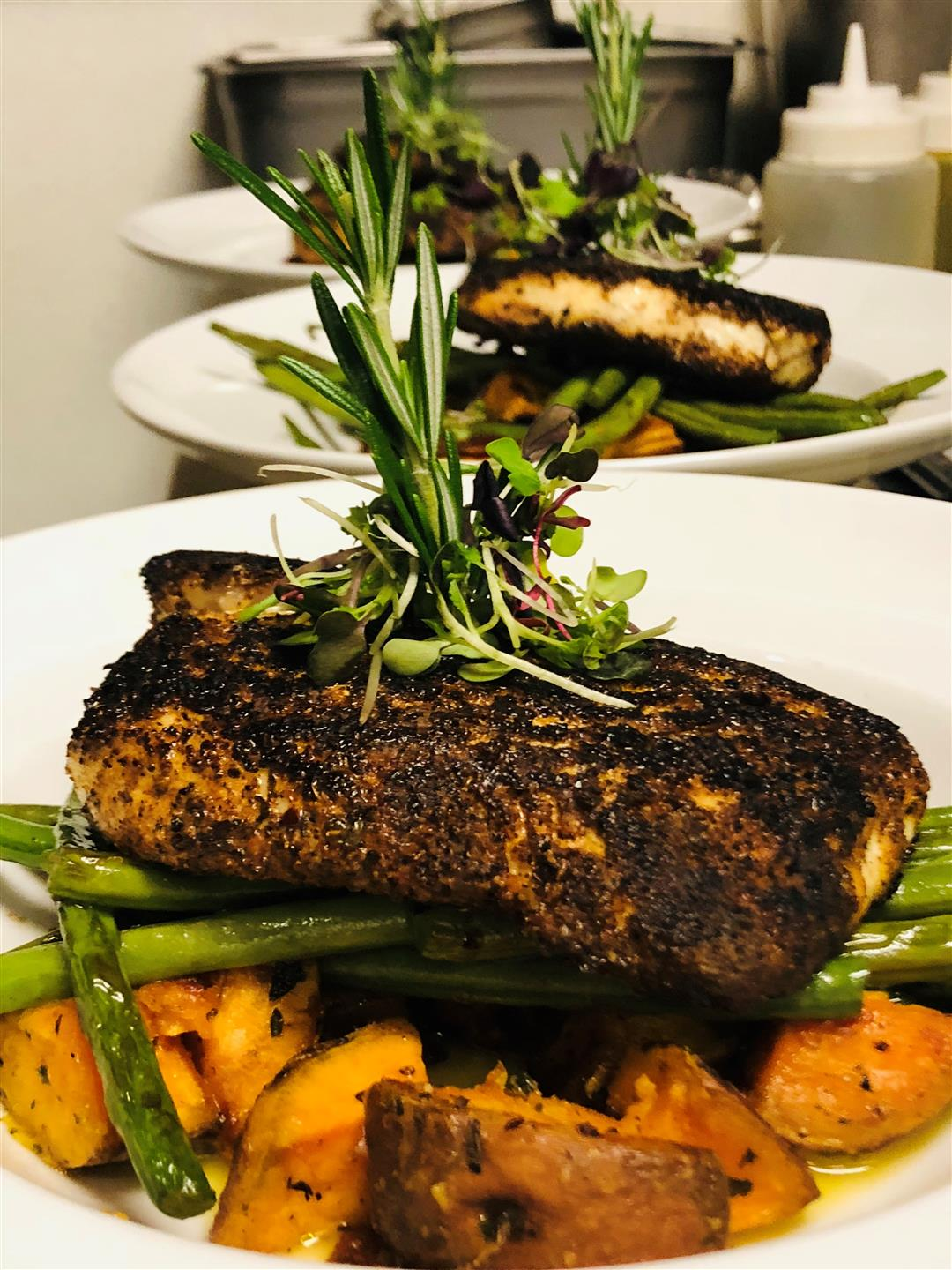 grilled fish on a bed of sweet potatoes and asparagus on a white plate