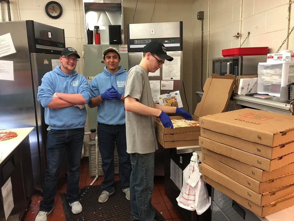 Three young employees working in a kitchen placing pizzas in boxes