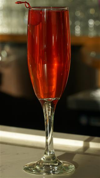 red cocktail in a champagn glass and garnished with a cherry