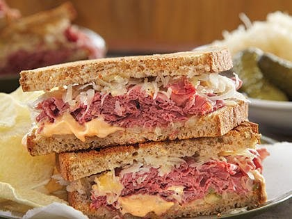 reuben sandwich topped with sauerkraut, and Russian dressing