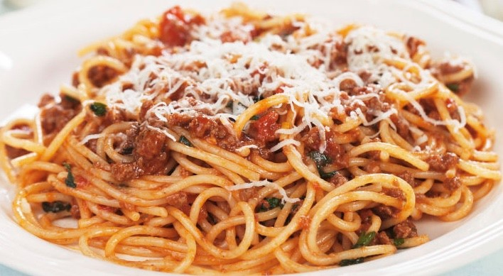 spaghetti and meatballs topped with cheese and tomato sauce