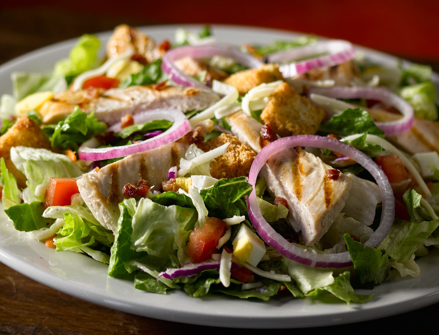 garden salad topped with chicken slices, onions, tomatoes and croutons