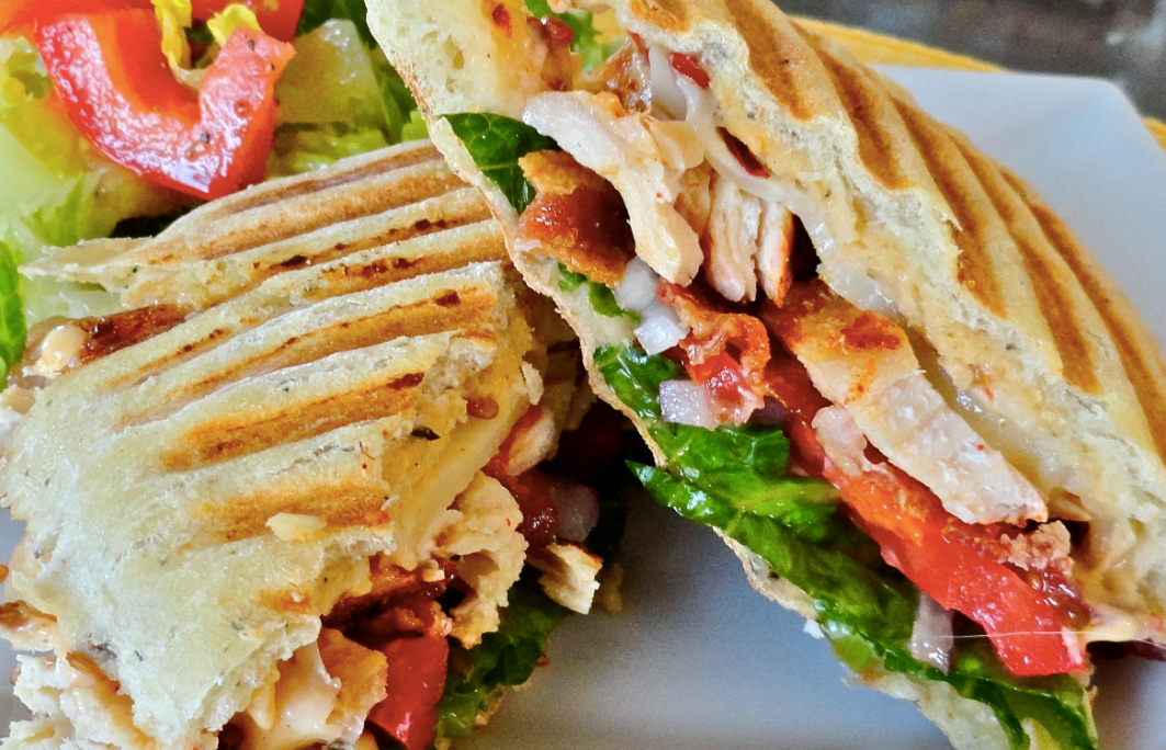 chicken panini topped with lettuce, tomatos and bacon